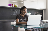 Young woman sitting at table in the kitchen working with laptop - MOMF000016