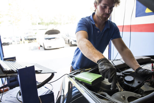 Mechanic placing a battery clip in a car - ABZF000941