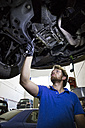 Mechanic fixing suspended car in his workshop - ABZF000953