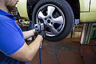 Mechanic fixing a car wheel in a workshop - ABZF000959