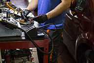 Mechanic fixing an electronic car parts in his workshop - ABZF000965
