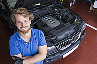 Confident mechanic standing in his car workshop with arms crossed - ABZF000968