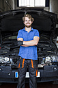 Confident mechanic standing in his car workshop with arms crossed - ABZF000971