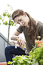Young woman gardening on balcony - PESF000266