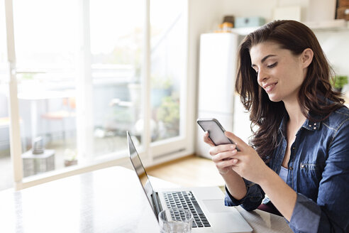 Smiling young woman at home using cell phone and laptop - PESF000275