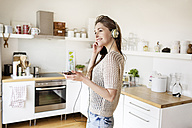 Smiling young woman in kitchen listening to music - PESF000278