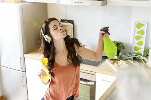 Young woman in kitchen cleaning and listening to music - PESF000281