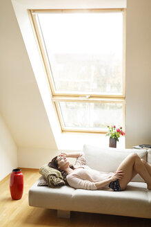 Relaxed woman lying on couch looking out of window - PESF000290