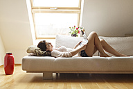 Relaxed woman lying on couch using laptop - PESF000293