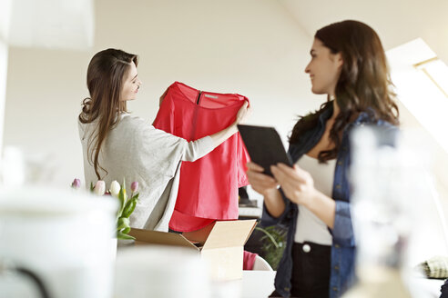 Two women with digital tablet and parcel with garment - PESF000299