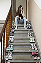 Young woman sitting on staircase with lots of shoes - PESF000305