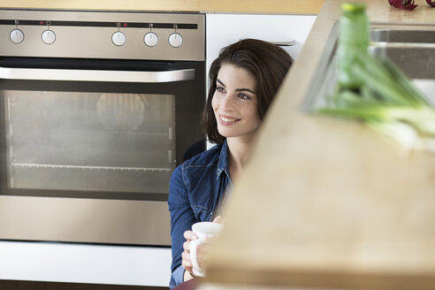 Young woman with cup of coffee relaxing in kitchen - PESF000308