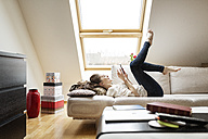 Happy woman lying on couch using cell phone - PESF000320