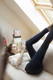 Smiling woman lying on couch using mobile device - PESF000335