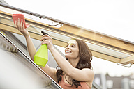 Smiling young woman cleaning roof window - PESF000338