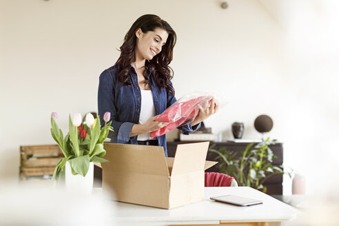 Smiling woman at home unpacking parcel with garment - PESF000341