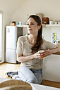 Young woman with cup of coffee relaxing in kitchen - PESF000350