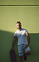 Smiling man with skateboard leaning against green wall - RAEF001360