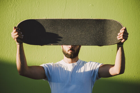 Man holding on his skateboard in front of his face - RAEF001366
