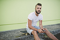 Portrait of man with smartphone sitting on his skateboard at carb - RAEF001369