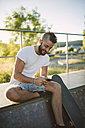 Smiling skateboarder using his cell phone in a skatepark - RAEF001375