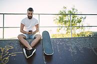 Skateboarder using smartphone in a skatepark - RAEF001378