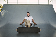 Smiling skateboarder sitting on ramp in a skatepark - RAEF001384