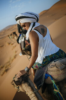Woman with turban riding a camel in the desert - KIJF000703