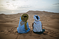 Woman sitting in the desert with Berber guide, watching sunset - KIJF000709