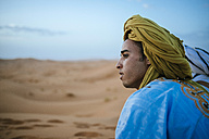 Yound berber sitting in desert, postrait - KIJF000712