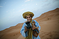 Young Berber taking pictures with camera - KIJF000715