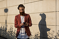 Fashionable young man standing in front of wall looking at smartphone - MAUF000727