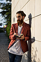 Fashionable young man with  notebook leaning against wall looking at distance - MAUF000730