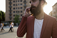 Young man with full beard telephoning with smartphone at backlight - MAUF000733