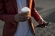 Man's hand holding coffee to go - MAUF000739