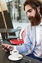 Stylish businessman using cell phone in a cafe - MAUF000748