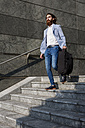 Stylish businessman walking with suitcase on stairs outdoors - MAUF000757