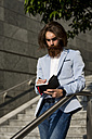 Stylish businessman writing in diary outdoors - MAUF000763