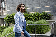Stylish businessman walking on stairs outdoors - MAUF000775