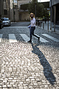 Stylish businessman walking on zebra crossing - MAUF000787