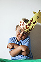 Portrait of smiling little boy wearing self-made headdress pulling funny faces - VABF000742
