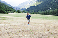 Happy little boy running on a mountain meadow - VABF000745