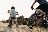 Back view of little boy and his great-grandfather on bicycle tour - JRFF000813
