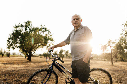 Senior man with bicycle standing on a field at evening twilight - JRFF000819
