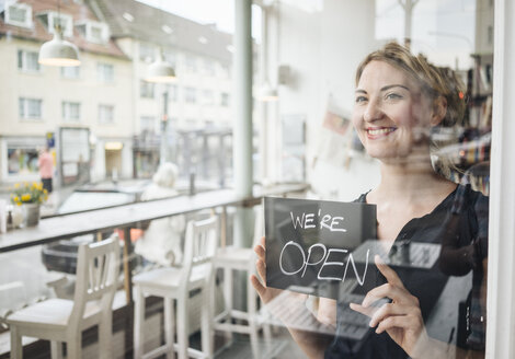 Smiling woman in a cafe attaching open sign to glass pane - KNSF000205