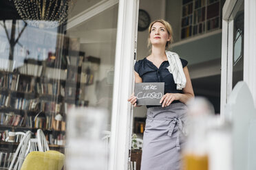 Woman in a cafe holding closed sign - KNSF000208