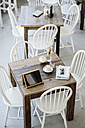 Digital tablet, sunglasses, newspaper and cup of coffee on table in a cafe - KNSF000214
