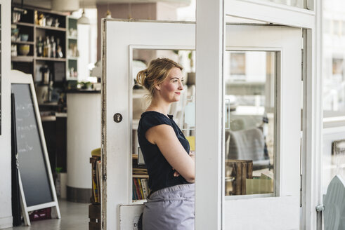 Smiling woman in a cafe looking out of window - KNSF000223