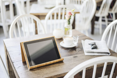 Digital tablet, sunglasses, newspaper and cup of coffee on table in a cafe - KNSF000229
