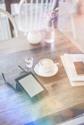E-book, sunglasses and cup of coffee on table in a cafe - KNSF000232